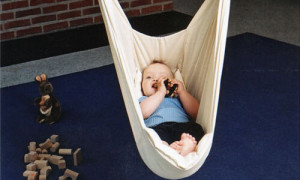 Baby spielt in der Federwiege